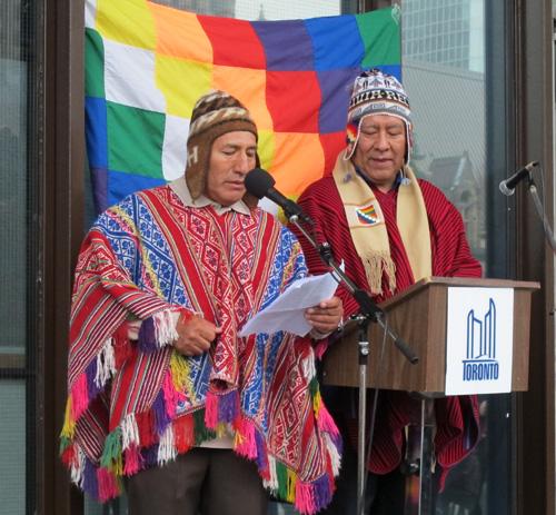 Jesus Leon (Quechua Peru) & Marco Guzman in front of Wiphala flag.