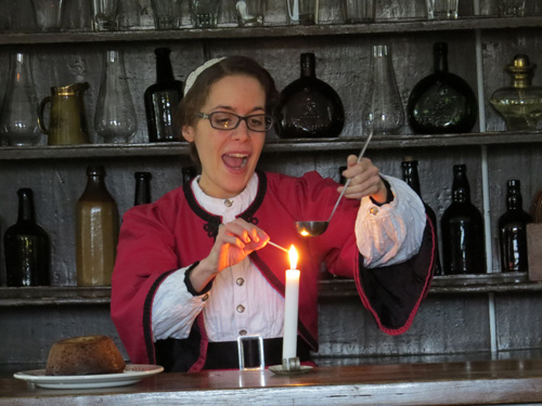 Ansley Newland, Historical Interpreter lights up a plum pudding at Black Creek Pioneer Village. Image Copyright ©2016 Ruth Lor Malloy